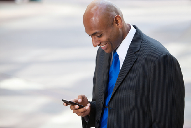 Portrait of an African American businessman text messaging